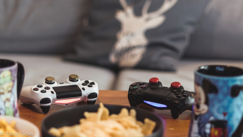 A couple dualshock 4 controllers next to some coffee and snacks